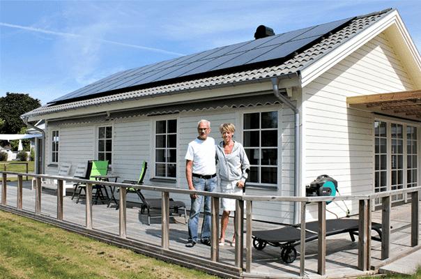Bild på två personer som står utanför et hur med solpaneler från Borås Elhandel på taket