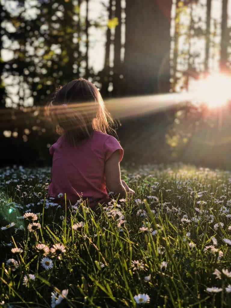 Ett litet barn som sitter på ängen och får solen i ansiktet