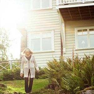 Stor villa där installation av bergvärmepumpar är möjlig. Kvinna går ner från villan.