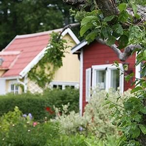 Två mindre hus i  grönskande område som ev har möjlighet att installera bergvärmepumpar.